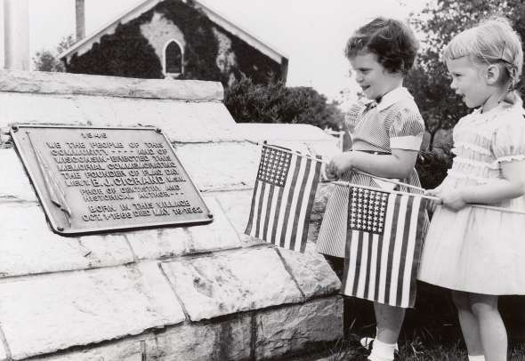 Two young girls hold American flags next to a plaque honoring Bernard J. Cigrand in Waubeka, Wisconsin, around 1949 as part of a Flag Day commemoration. UW Digital Collections